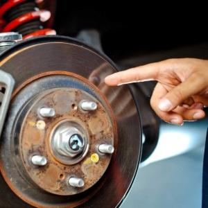 Mechanic inspecting brake pads and rotor